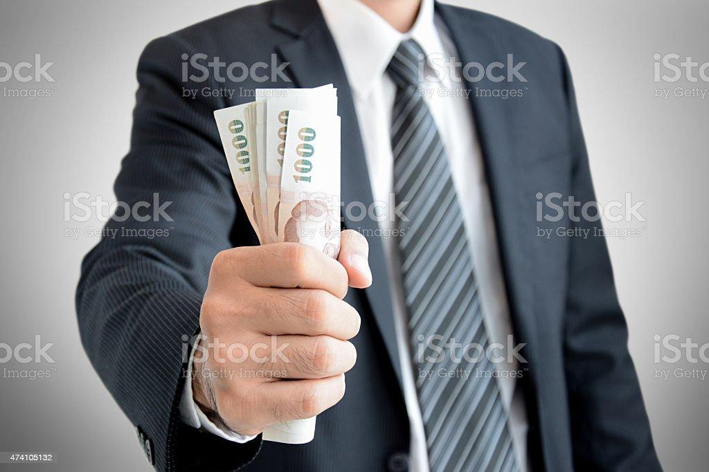 Businessman hand grabbing money - Thai Baht (THB) stock photo