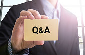 businessman hand holding a business card with a message Q&A