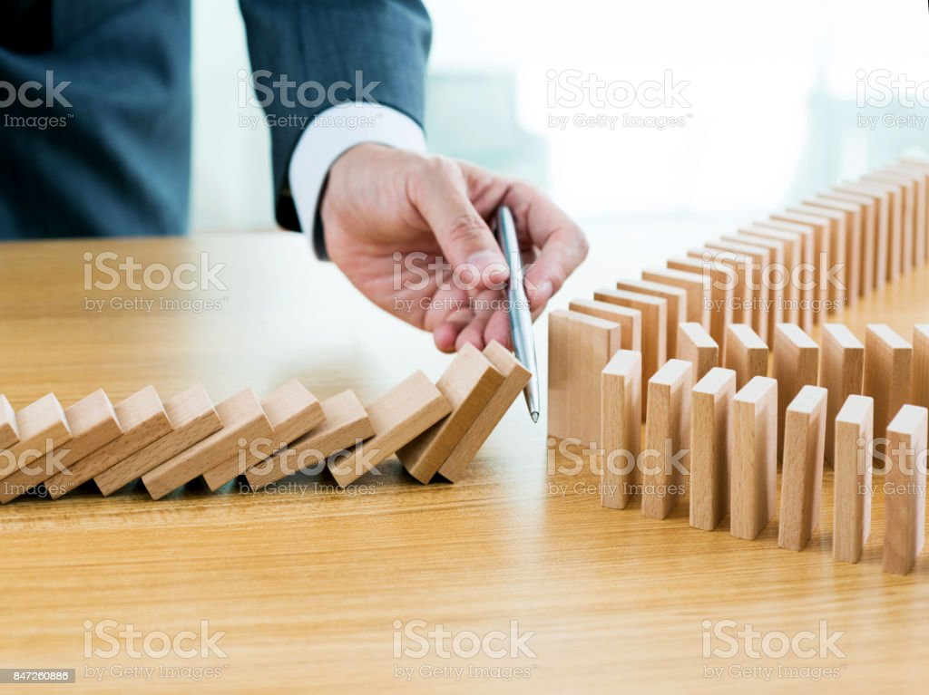 Businessman hand holding a pen stop domino effect