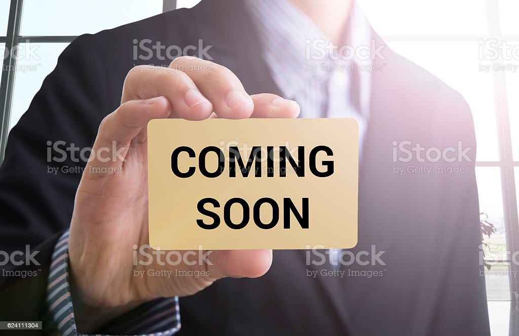 businessman hand holding business card with message coming soon stock photo