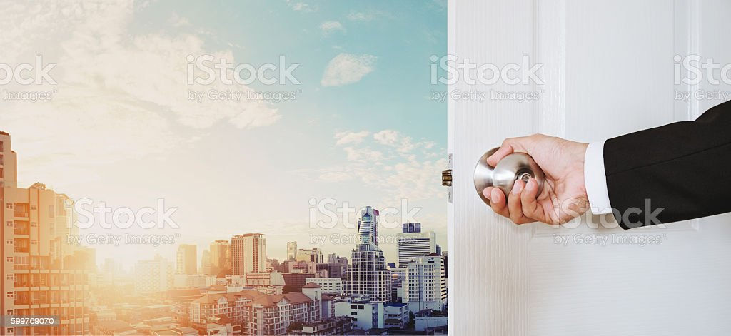 Businessman hand holding door knob opening, with Bangkok cityscape stock photo
