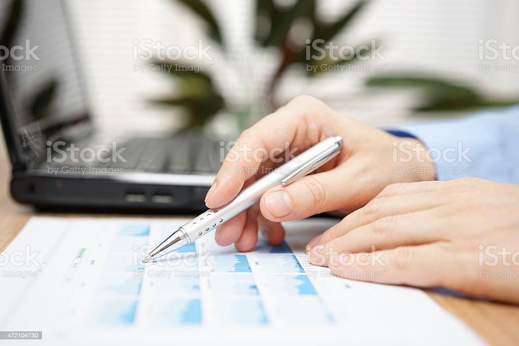 Businessman hand holding pen over business analyze stock photo