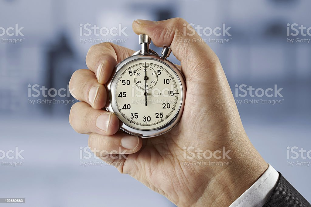 Businessman hand holding stopwatch stock photo