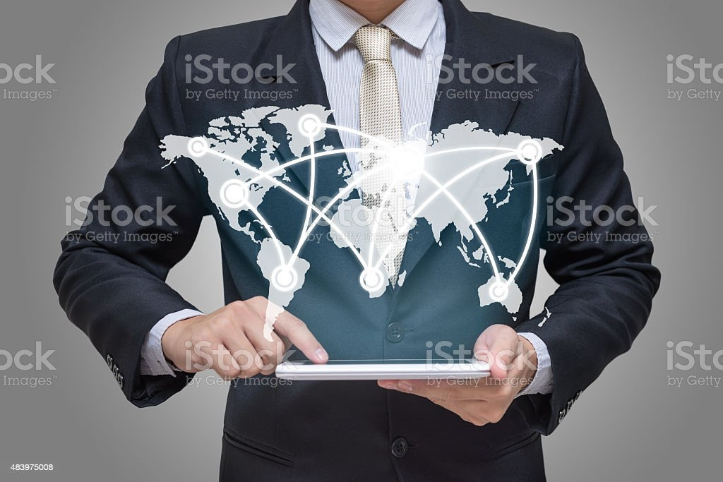 Businessman hand holding tablet global marketing on gray background stock photo
