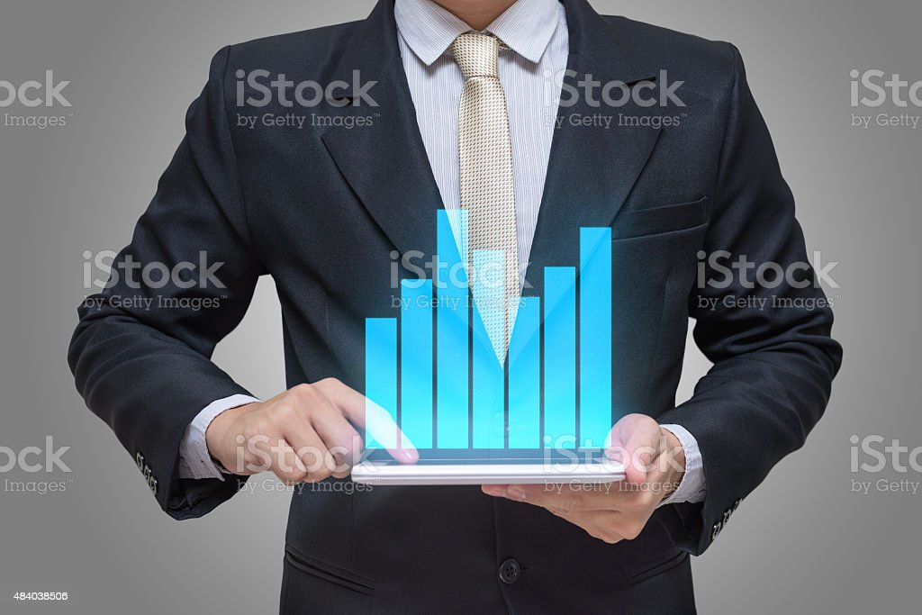 Businessman hand holding tablet graph finance on gray background stock photo