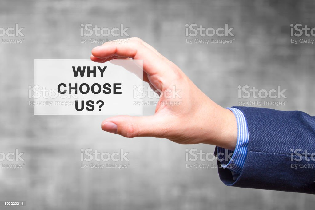 Businessman hand holding Why Choose Us? sign isolated on grey background. Business concept. Stock Photo stock photo