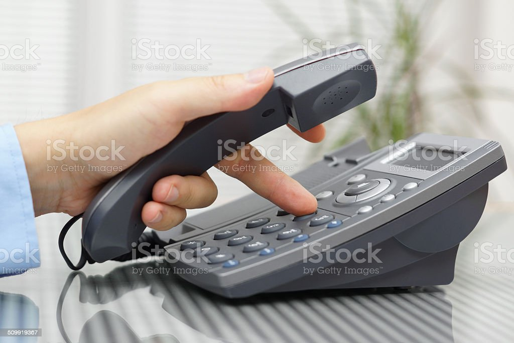 businessman hand is dialing  phone number with picked up headset stock photo