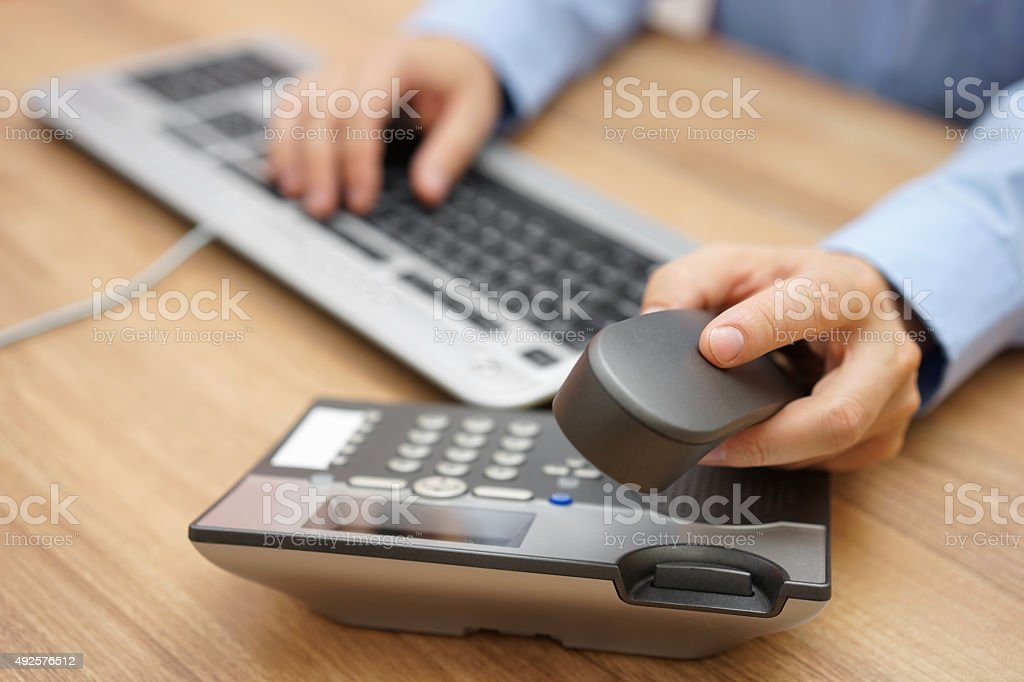 businessman hand picking up telephone receiver on business workplace stock photo