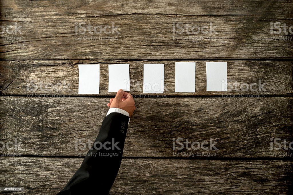 Businessman hand placing five blank white  cards in a row stock photo