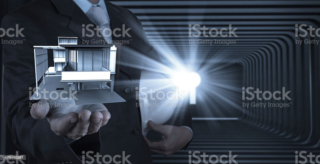 businessman hand presents house model on modern computer royalty-free stock photo