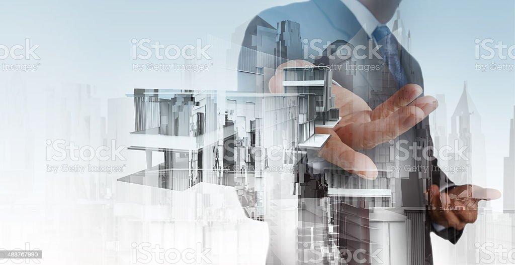 businessman hand presents house model on modern computer stock photo