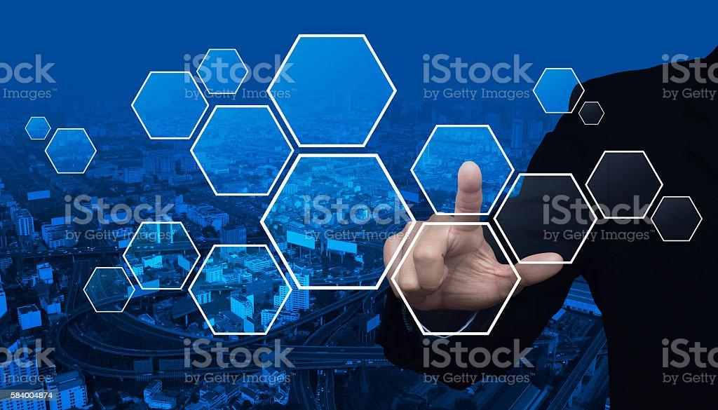 Businessman hand pushing blank hexagon shape screen over city tower stock photo