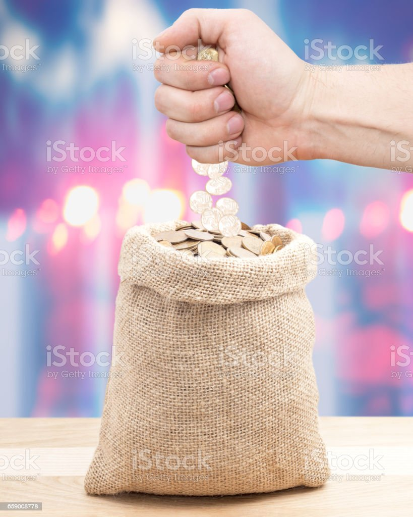 A businessman hand put coins in the bag with money stock photo