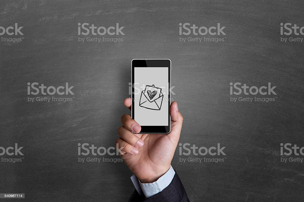 businessman hand showing heart shaped envelop stock photo
