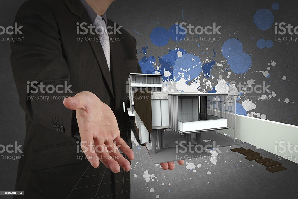 businessman hand shows house model and splash colors royalty-free stock photo