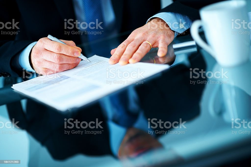 Businessman hand signing contract paper at the desk stock photo