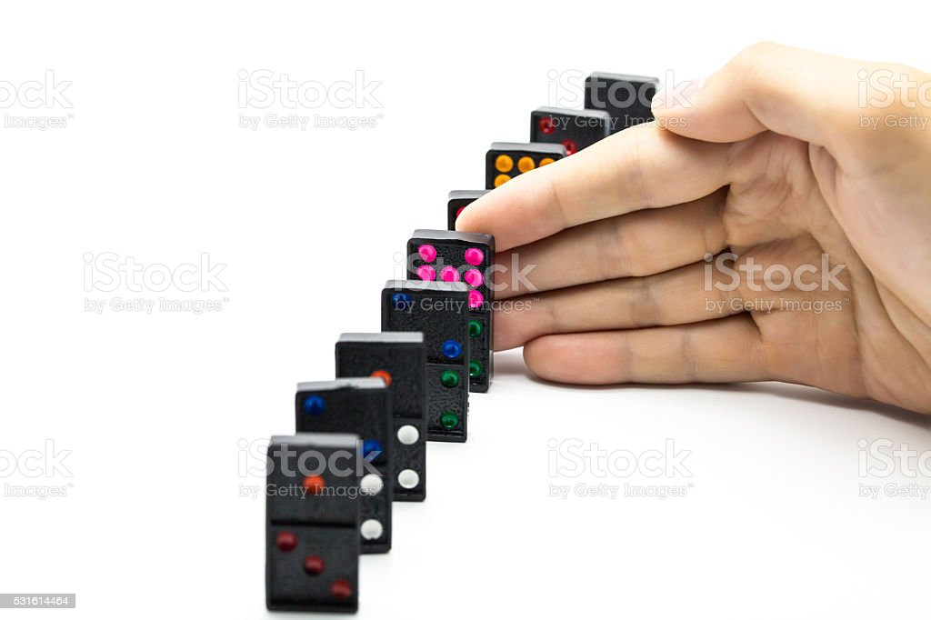 Businessman hand stopping domino effect on isolated white backgr stock photo