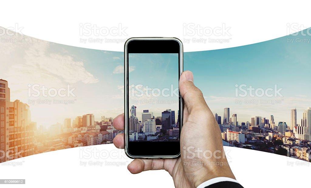 Businessman hand taking panoramic photo of Bangkok cityscape in sunrise stock photo