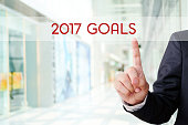 Businessman hand touch 2017 goals over blur office background