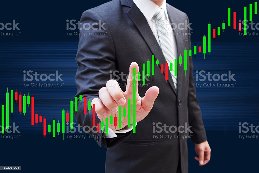 Businessman hand touching Candlestick Chart, investment concept stock photo