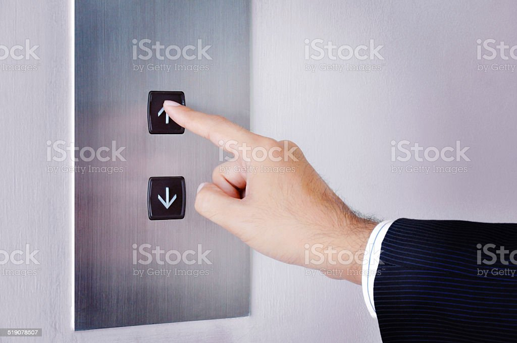 Businessman hand touching going up sign on lift control panel stock photo