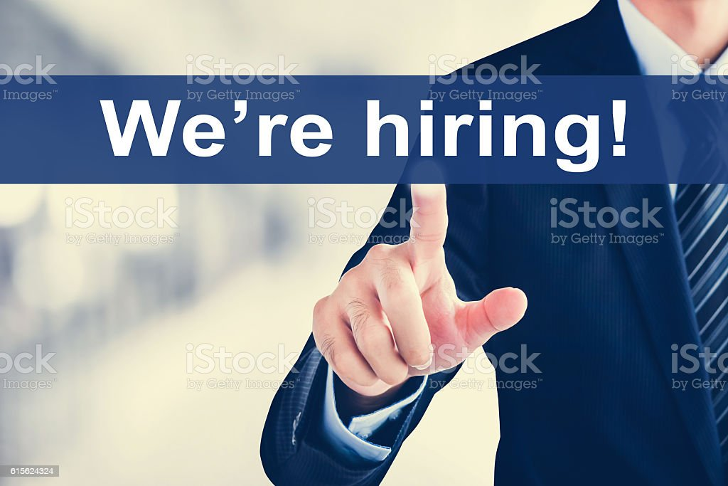 Businessman hand touching We're hiring! message on virtual scree stock photo