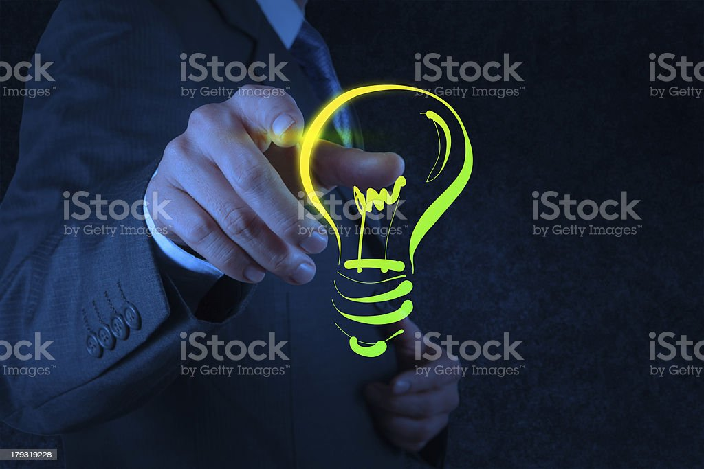 businessman hand with a pen drawing light bulb royalty-free stock photo