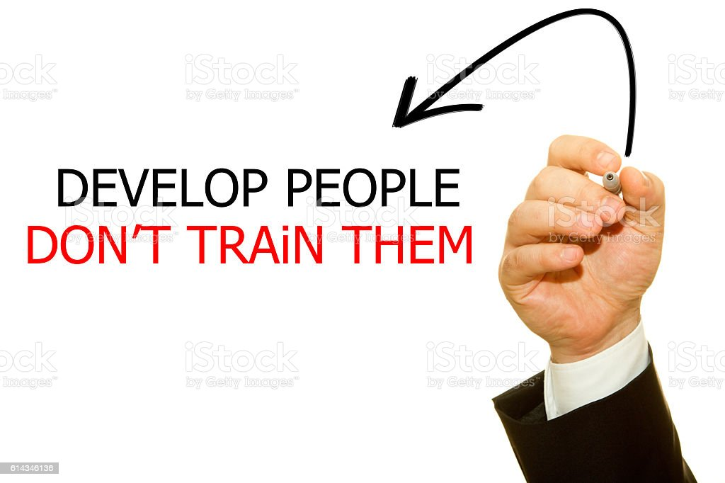Businessman hand writing Develop People Don't Train stock photo