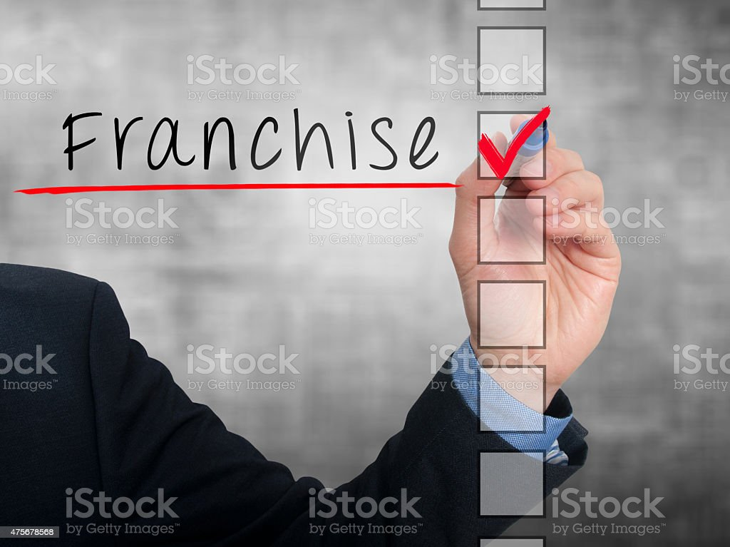 Businessman hand writing Franchise and check listing task stock photo