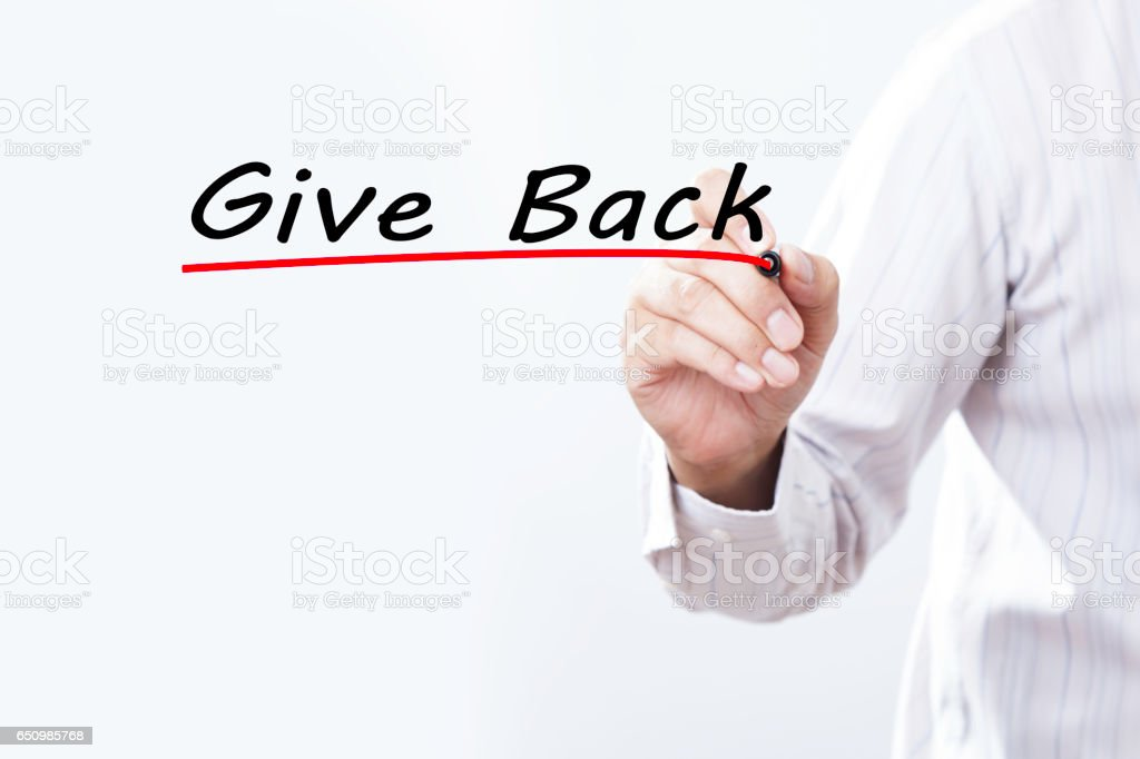 Businessman hand writing give back with marker, Business concept stock photo