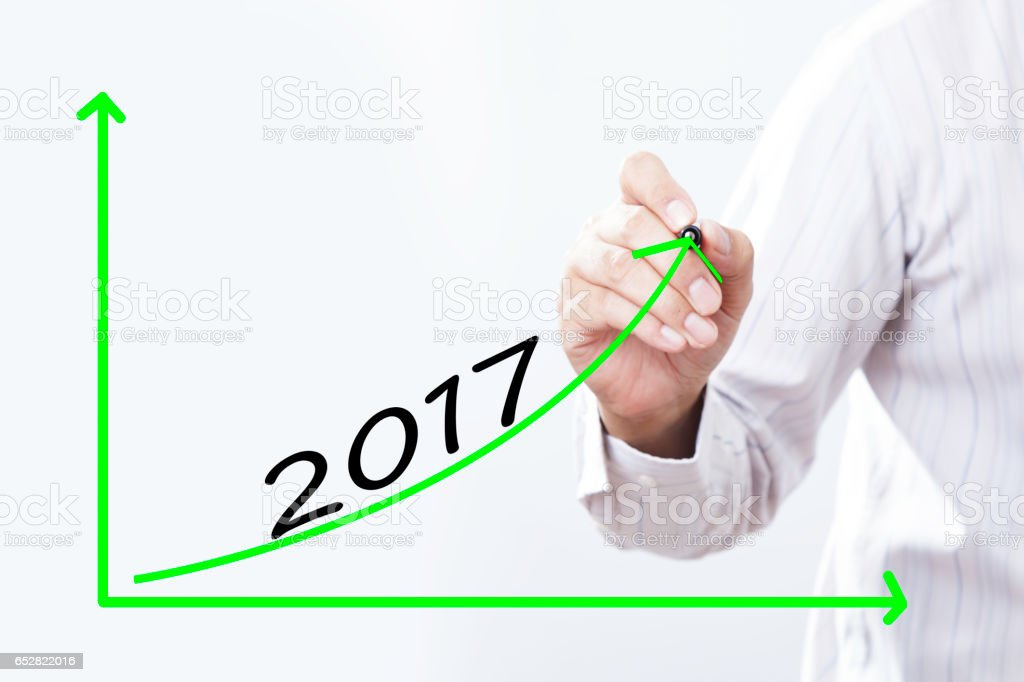 Businessman hand writing growth graph for year 2017  with red marker on transparent wipe board, business concept. stock photo