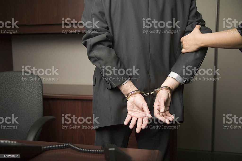 Businessman handcuffed and being lead away stock photo