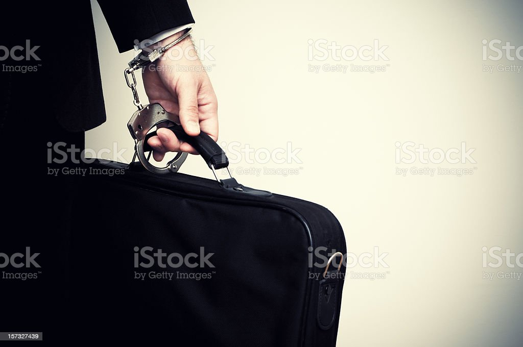 Businessman handcuffed to briefcase royalty-free stock photo