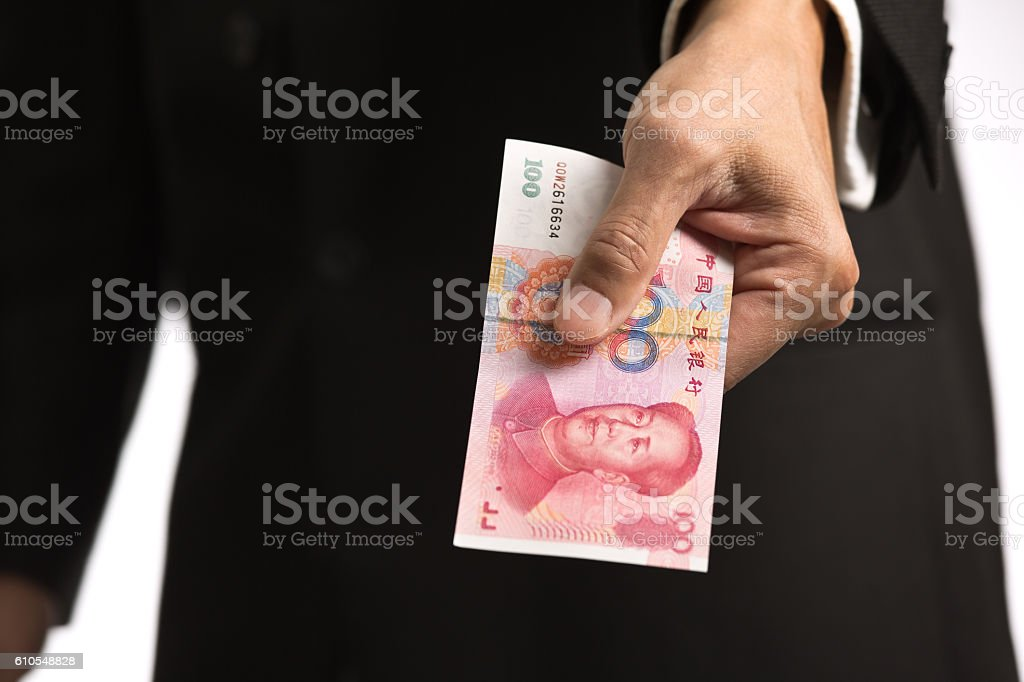 Businessman Handing a Chinese currency to Viewer stock photo