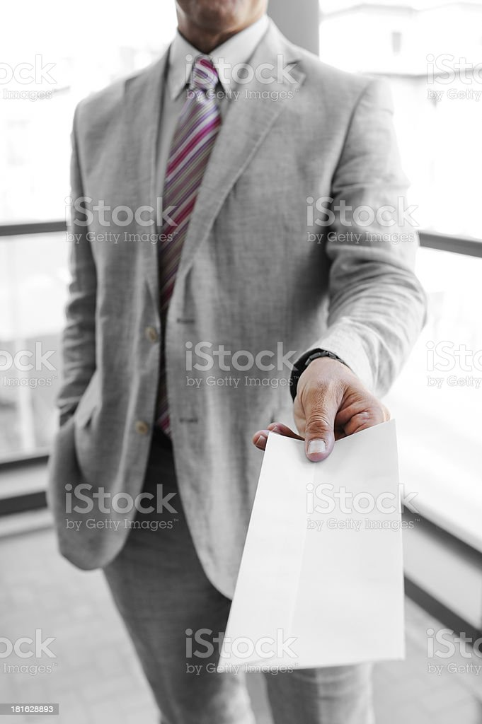 Businessman handing a mailing envelope royalty-free stock photo
