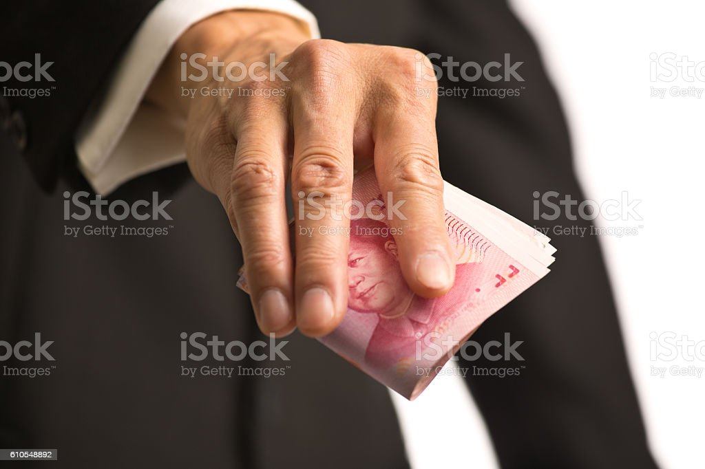 Businessman Handing a Stack of Chinese currency to Viewer stock photo
