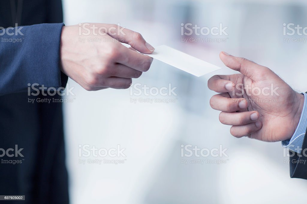 Businessman handing business card to colleague in office stock photo