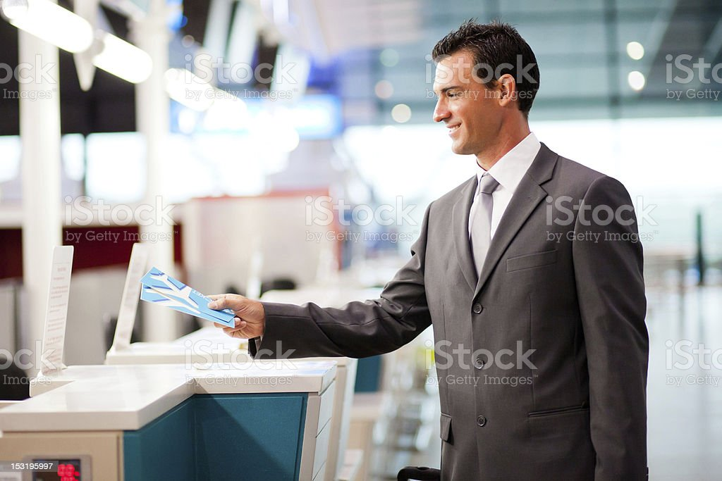 businessman handing over air ticket at airline check in counter stock photo