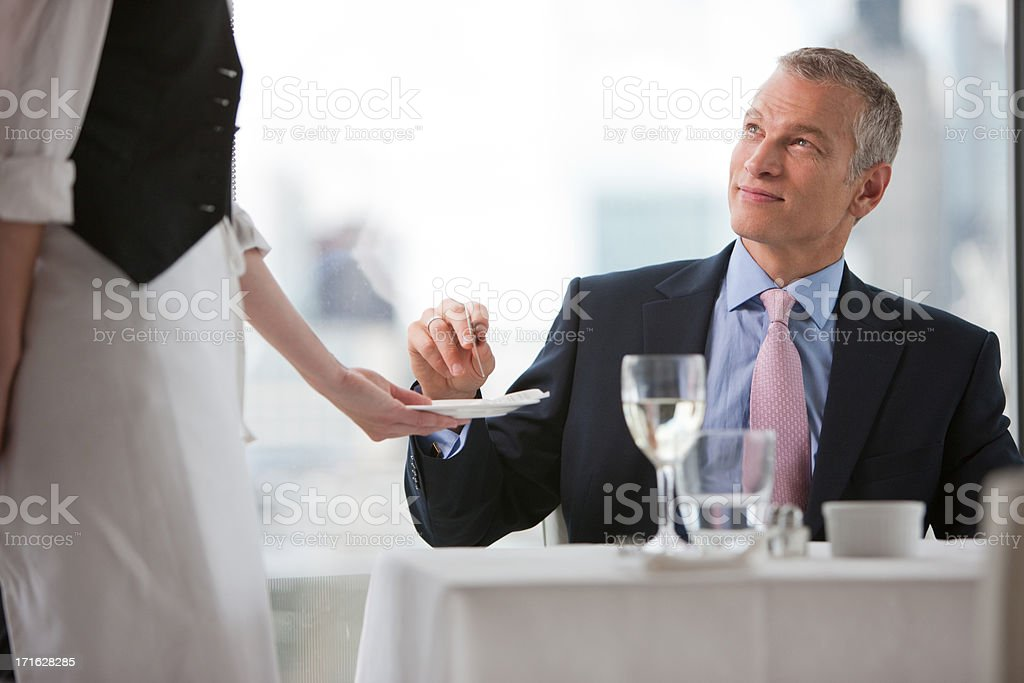 Businessman handing waitress credit card in restaurant stock photo