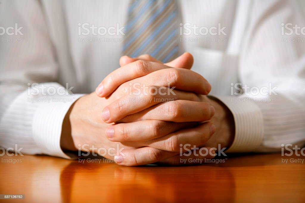 Businessman hands clasped stock photo