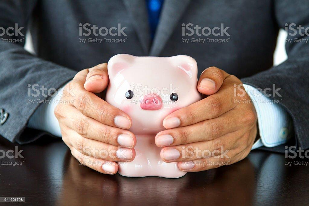Businessman hands covering piggybank stock photo