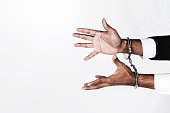 Businessman hands fettered with handcuffs isolated on white with