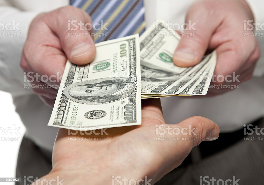 Businessman hands handing money to other hand stock photo