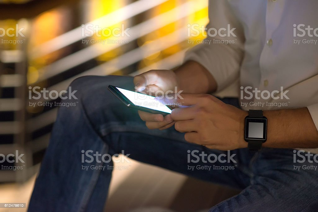 Businessman Hands holding smartphone at night outside stock photo