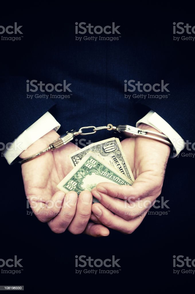 Businessman Hands in Handcuffs Hold Ten Dollar Bill stock photo