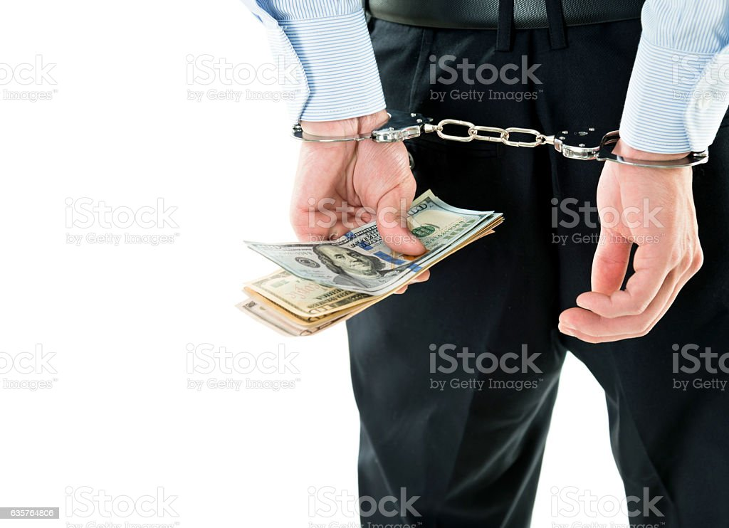 Businessman hands in handcuffs holding US dollars stock photo