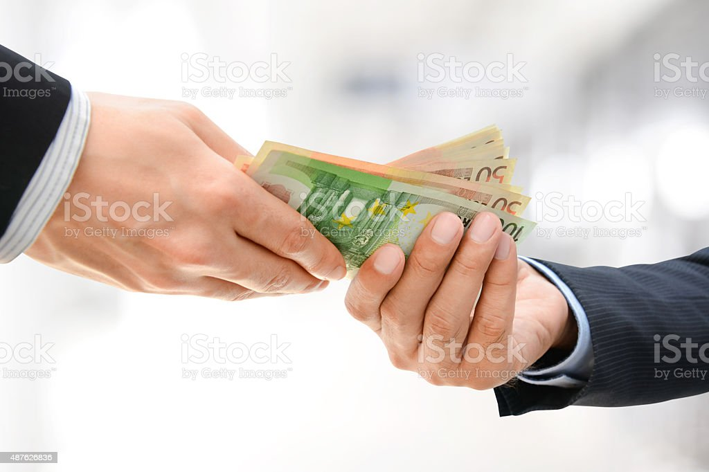Businessman hands passing money, Euro currency (EUR) stock photo