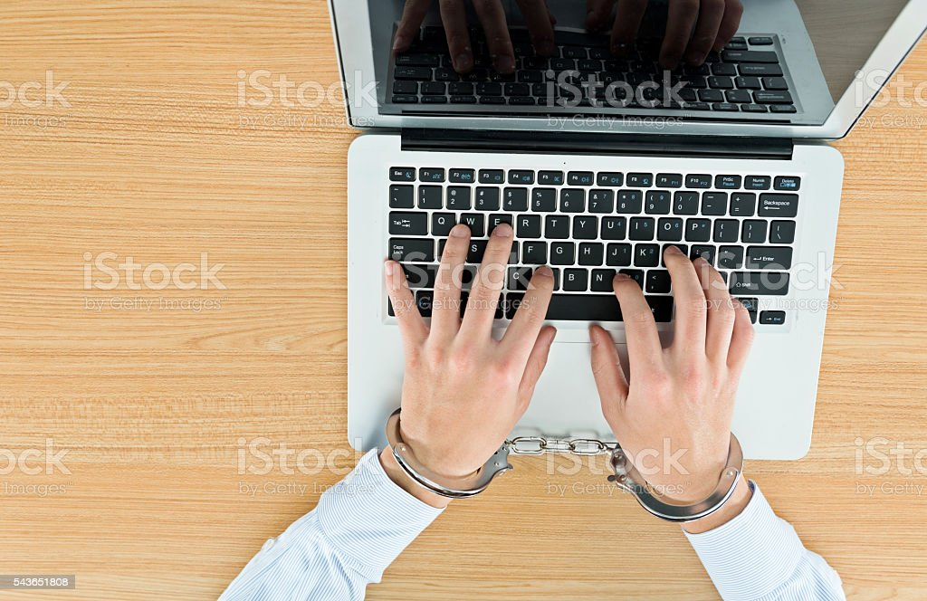 Businessman hands tied with handcuffs on laptop keyboard stock photo