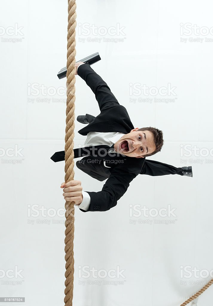Businessman hanging from rope stock photo