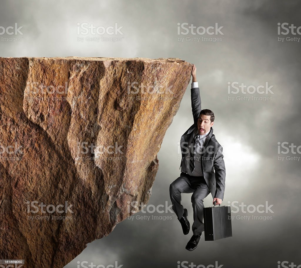 Businessman hanging on for dear life from edge of cliff royalty-free stock photo